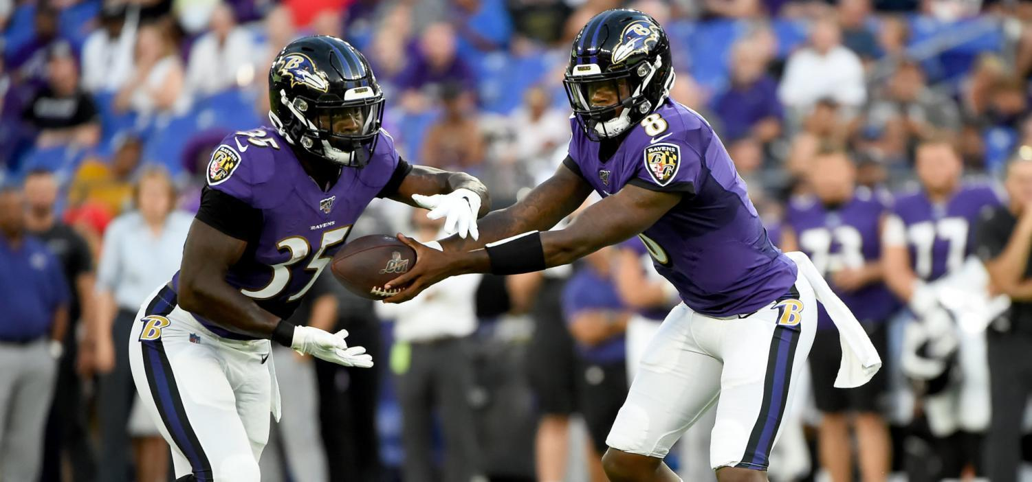 Quarterback Lamar Jackson hands the ball off to Running Back Gus Edwards during a home game at M&T Bank Stadium.