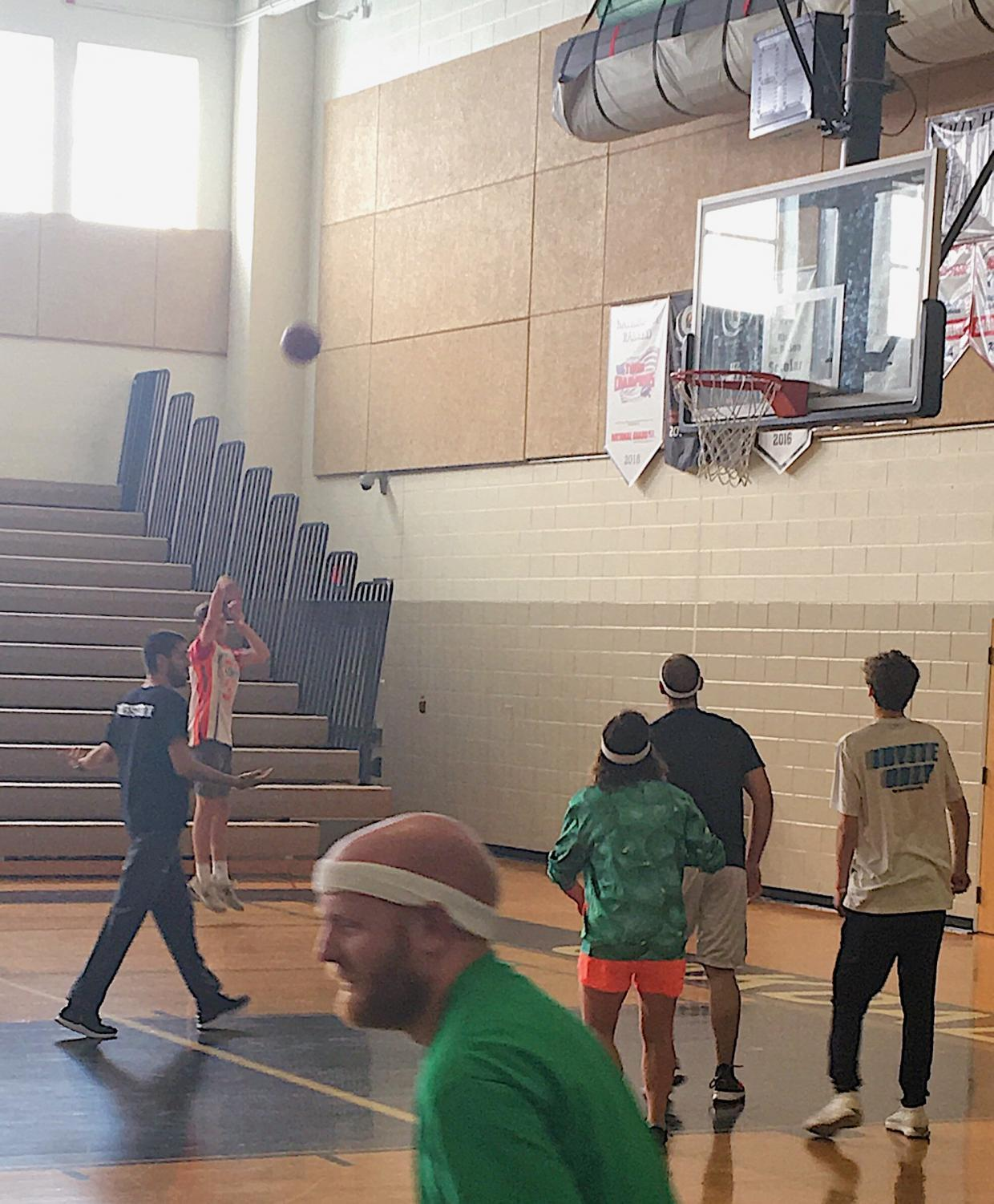 A student makes a shot during the basketball game, which raised funds for the Environmental Club's newest project.