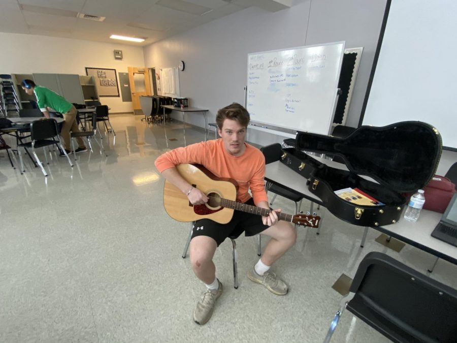 Senior Evan Hayek practices his guitar during some spare time in journalism. Putting on a show for his classmates.
