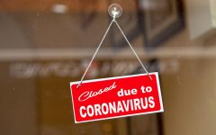 Red sign hanging at the glass door of a shop saying