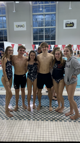 Swimmers on the Oakdale High School 2019 Swim Team pose in front of UMAC pool.