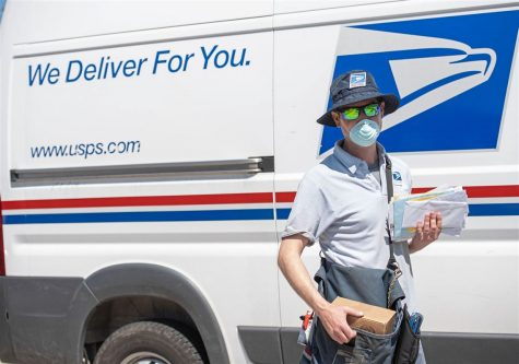 A postal worker in front of his work truck.