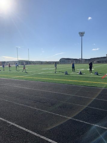 Girls track team is warming up on a sunny day to get ready for their season.  Everyone still socially distanced due to the regulation with return to play.