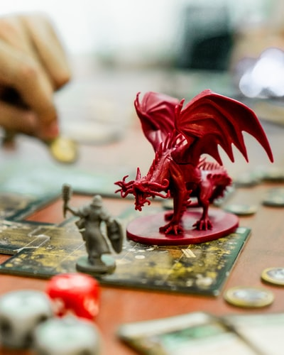 Figurines of a player's character and a dragon enemy laid out on a map for a game of D&D. Sometimes people like to have visual representations of in-game characters and locations while playing.