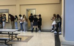 Students wait in a line that goes outside the cafeteria to get lunch.