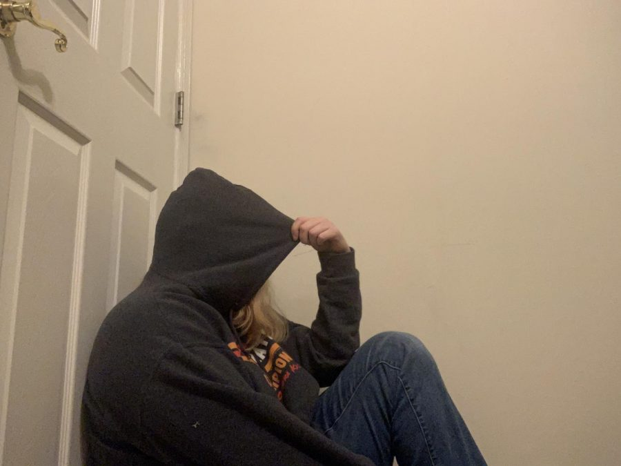 A teen sitting isolated against the wall, not wanting her face to be seen.